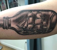 black and grey realism ship in a bottle tattoo