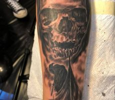 black and grey realism skull sleeve tattoo