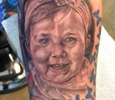 black and grey realism baby portrait tattoo
