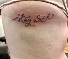 script lettering rib tattoo Geneva NY